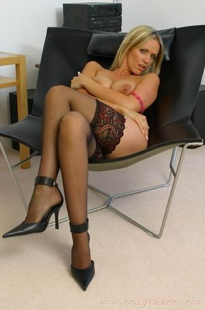 blonde in armchair teasing with her sexy legs