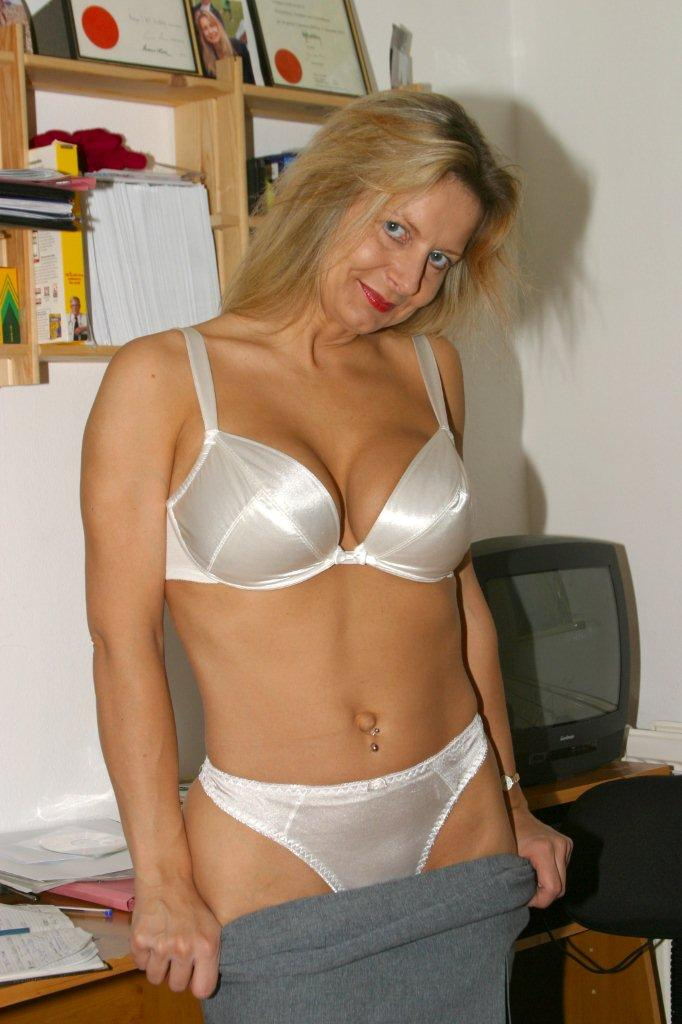 horny mature blonde posing on the desk with her legs wide open to show her juicy